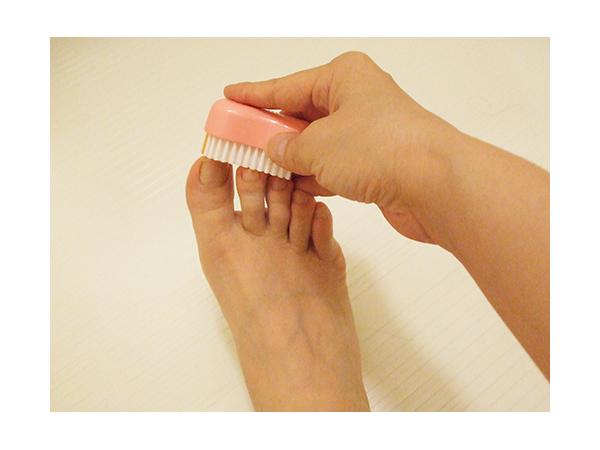 足指を爪ブラシで洗浄